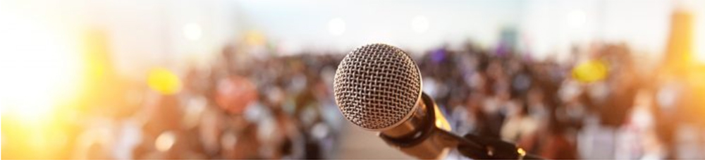 Closeup of microphone with blurred crowd in the background